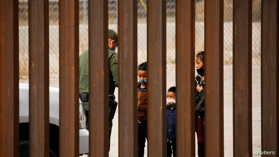 Migrants are detained by a U.S. Border Patrol agent after crossing the Rio Bravo river to turn themselves in to request for…