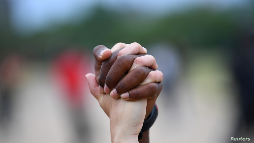 """FILE - A man and a woman hold hands aloft in Hyde Park during a """"Black Lives Matter"""" protest."""