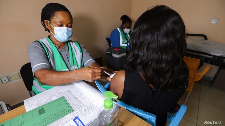 A medical worker injects the AstraZeneca's coronavirus disease (COVID-19) vaccine to a woman at the Nationa Hospital in Abuja.