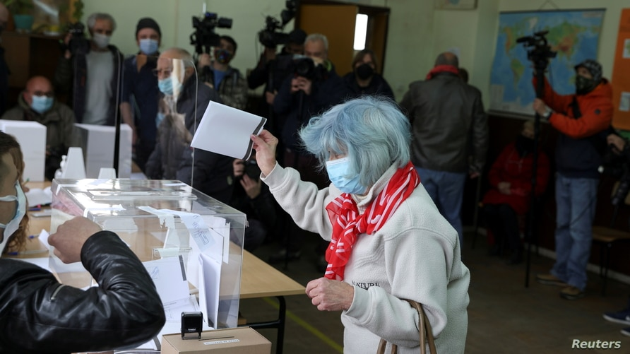 A woman casts her ballot at a polling station during the parliamentary election, in Sofia, Bulgaria, April 4, 2021.