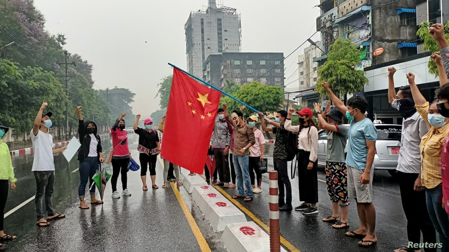 Anti-coup protesters hold a Chinese flag before burning it down during a demonstration against China in Yangon, Myanmar, April 5, 2021.