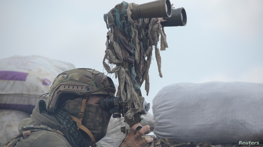 A service member of the Ukrainian armed forces uses binoculars while observing the area at fighting positions on the line of…