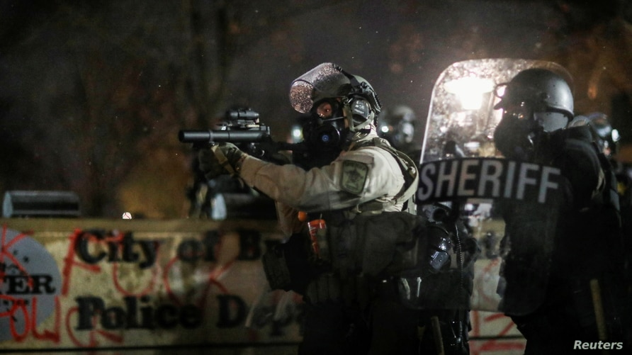 A police officer holds a tear gas launcher while standing guard at the Brooklyn Center Police Department, days after Daunte…
