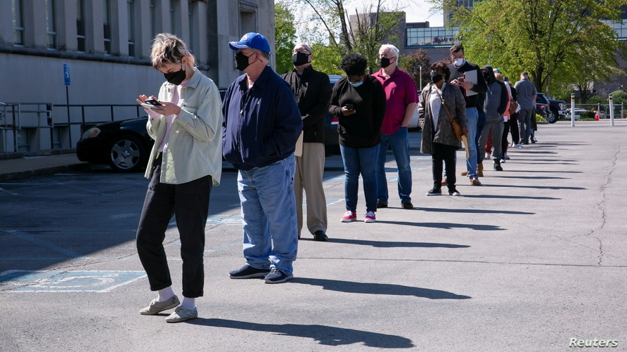 People line up outside a newly reopened career center for in-person appointments in Louisville, U.S., April 15, 2021.  REUTERS…