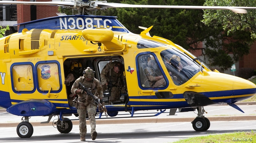 Law enforcement personnel exit a helicopter after it dropped them off next to the Arboretum Oaks apartment complex, the scene…