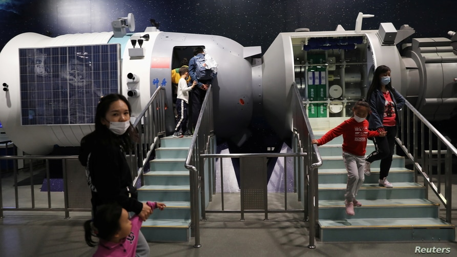 Visitors walk near a model of space laboratory at an exhibition featuring the development of China's space exploration on the…
