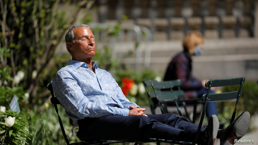 A person sits in Bryant Park after the Centers for Disease Control and Prevention (CDC) announced new guidelines regarding…