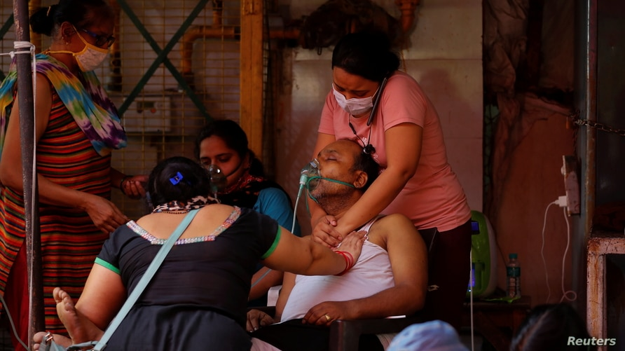Manisha Bashu (R) and her mother press the chest of her father, who is suffering from breathing problem, after he felt…