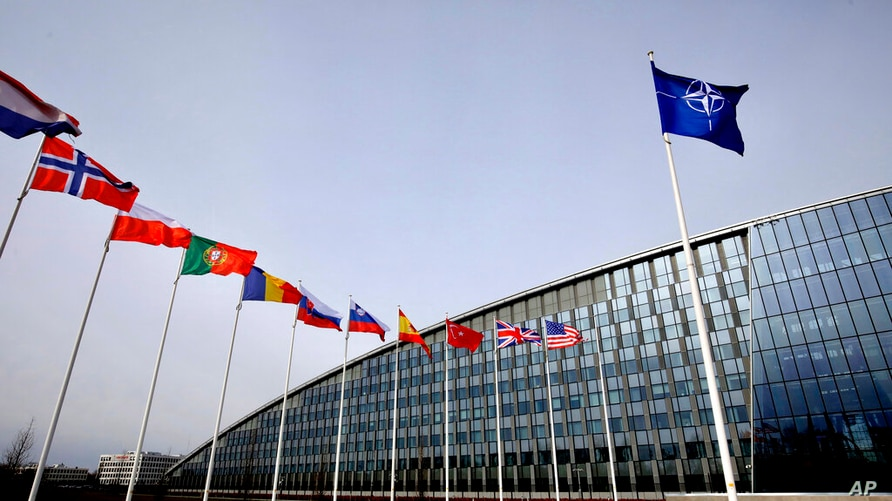 FILE - In this Friday, Feb. 28, 2020 file photo, flags of NATO alliance members flap in the wind outside NATO headquarters in…