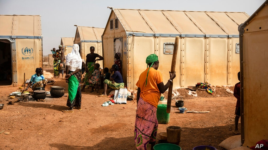 Displaced women prepare food Monday Feb. 8, 2021 in the Kaya camp, 100 kms North of Ouagadougou, Burkina Faso.  A report by…