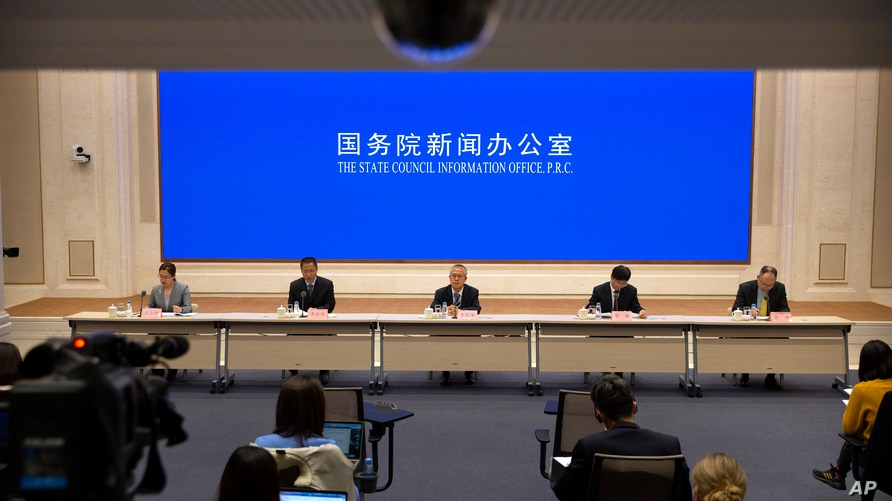 Chinese academics and government officials attend a press conference about a Chinese government-issued report on human rights…