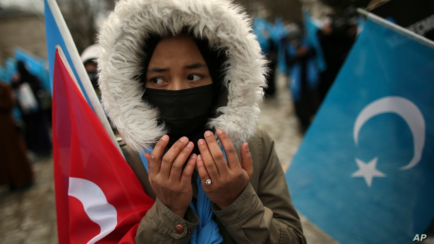 FILE - A protester from the Uyghur community living in Turkey prays during a protest against the visit of China's Foreign Minister Wang Yi to Turkey, in Istanbul, March 25, 2021.