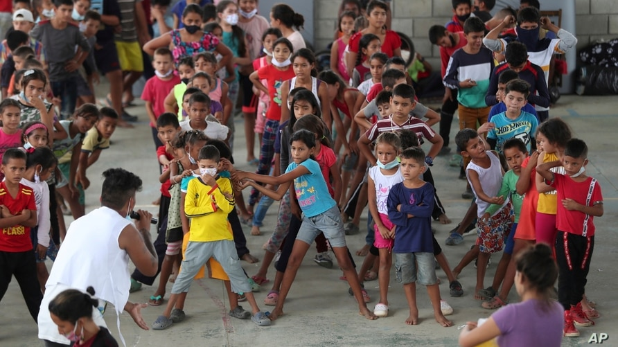 FILE - Children who traveled with their families from Venezuela play at the shelter in Arauquita, Colombia, March 25, 2021, on the border with Venezuela.