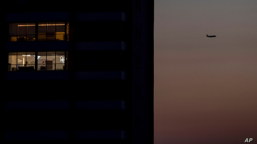 A passenger plane flies over the capital city of Beirut that remains in darkness during a power outage, Lebanon, Monday, March…