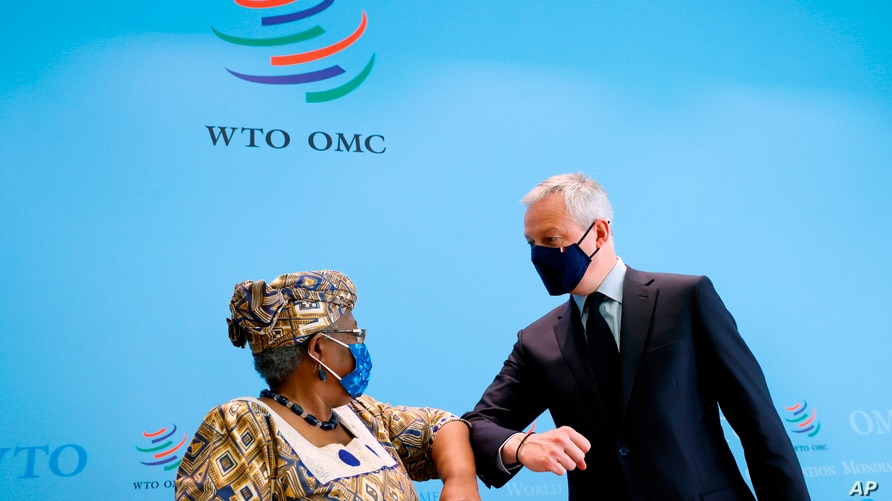 French Finance Minister Bruno Le Maire, right, and World Trade Organisation (WTO) Director-General Ngozi Okonjo-Iweala, left, elbow-bump after a joint news conference at WTO headquarters in Geneva, April 1, 2021.