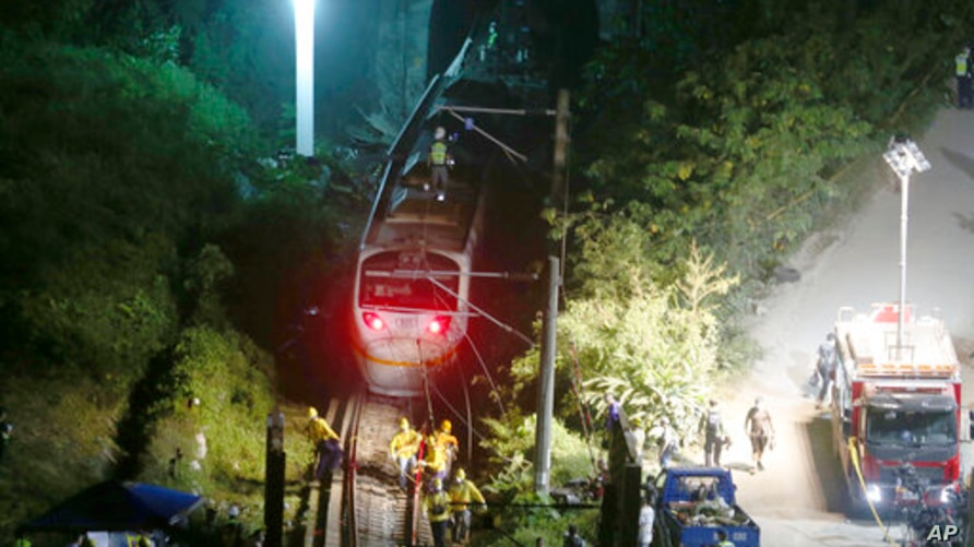 Rescue workers work at the derailed train near Taroko Gorge in Hualien, Taiwan on Friday, April 2, 2021. The train partially…