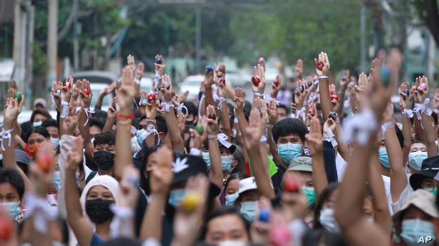 Anti-coup protesters raise decorated Easter eggs along with the three-fingered symbols of resistance during a protest against the military coup on Easter, April 4, 2021, in Yangon, Myanmar.