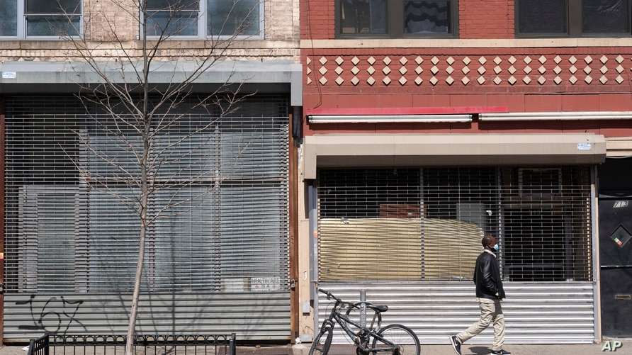 Two storefronts are empty, Monday, April 5, 2021 in New York. (AP Photo/Mark Lennihan)