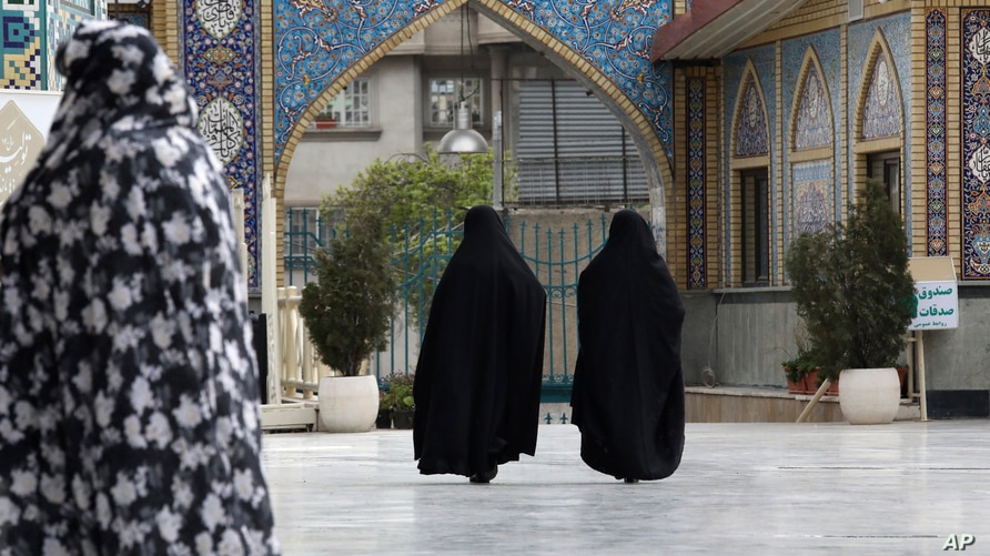 Head-to-toe veiled Iranian women walk at the shrine of Saint Saleh in northern Tehran, Iran, Tuesday, April 6, 2021.   (AP…