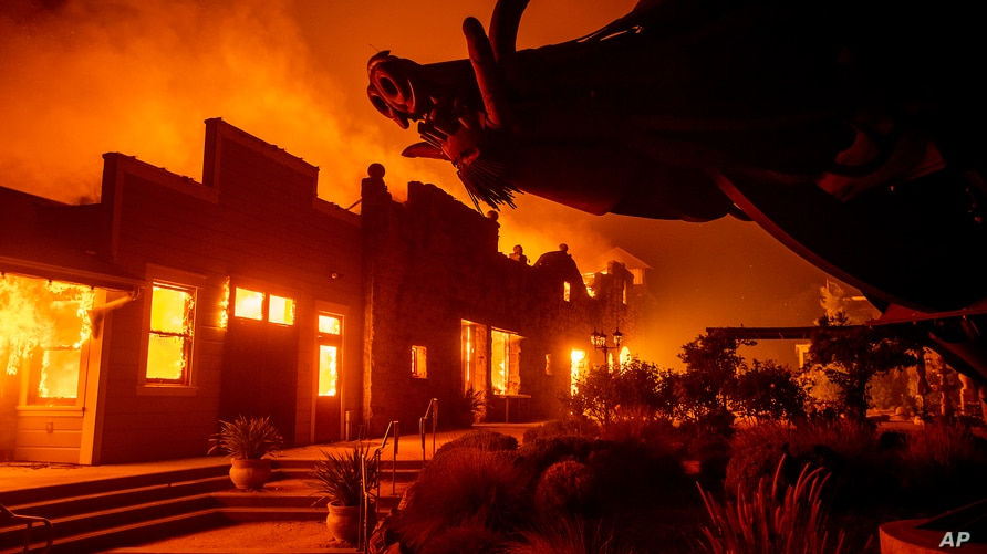 FILE - In this Oct. 27, 2019, file photo, flames from the Kincade Fire consume Soda Rock Winery in Healdsburg, Calif. A California prosecutor has charged troubled Pacific Gas & Electric with starting a 2019 wildfire.