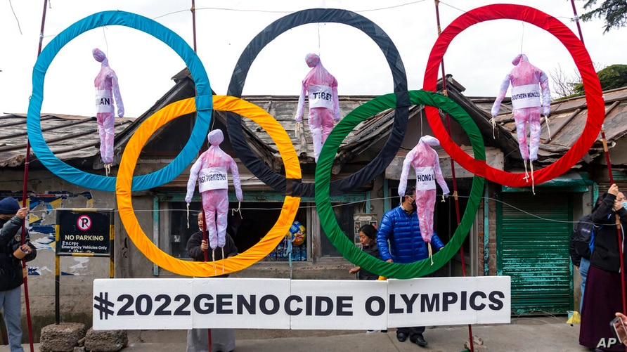 FILE - In this Feb. 3, 2021, file photo, exile Tibetans use the Olympic Rings as a prop as they hold a street protest against…