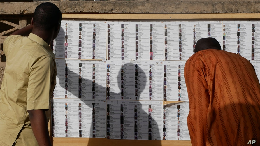 Voters check their names on a list before casting their ballot at a polling station in N'djamena, Chad, Sunday April 11, 2021…