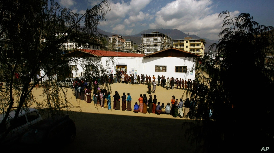 FILE- In this March 24, 2008 file photo, Bhutanese people queue up to cast their votes outside a polling station, in Thimphu.