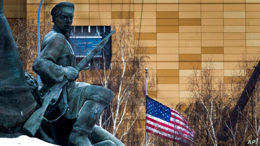 FILE - In this file photo taken on Friday, Dec. 30, 2016, The U.S. Embassy with its national flag, seen behind a monument to…