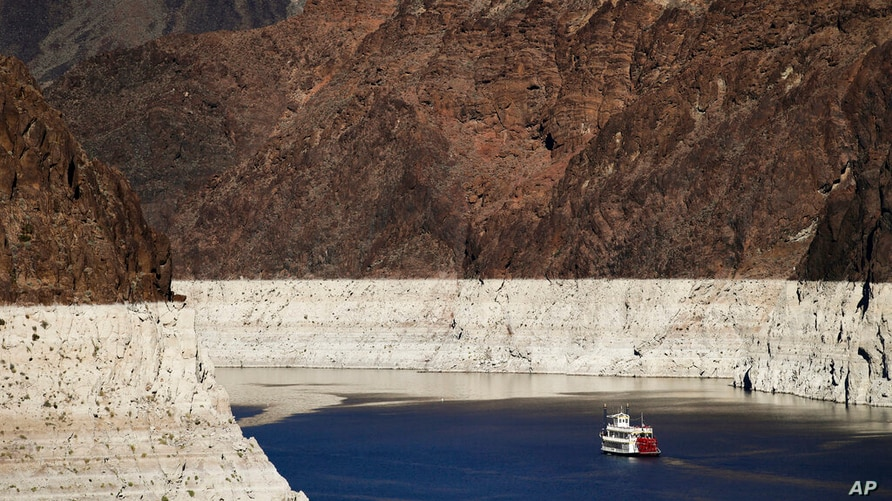 FILE - In this Oct. 14, 2015, file photo, a riverboat glides through Lake Mead on the Colorado River at Hoover Dam near Boulder…