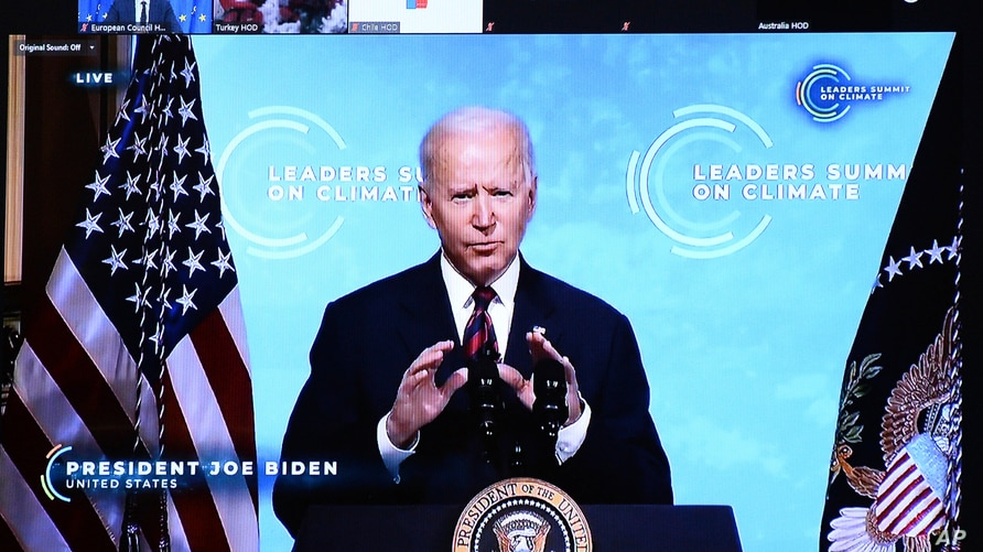 U.S. President Joe Biden is seen on a screen as European Council President Charles Michel attends a virtual Global Climate…