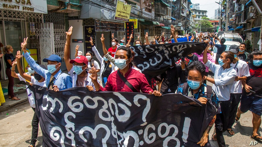 """Anti-coup protesters hold a banner that reads """"What are these? We are Yangon residents!"""" as they march during a demonstration…"""