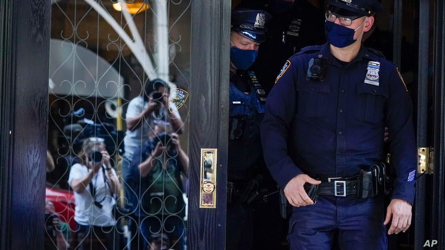 Members of the media are reflected in the widow a door as New York City Police officers walk out of the apartment building…