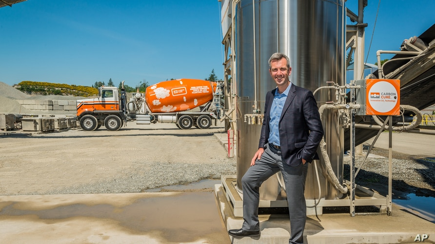 CarbonCure CEO and Founder Rob Niven standing with a CarbonCure system and branded concrete truck