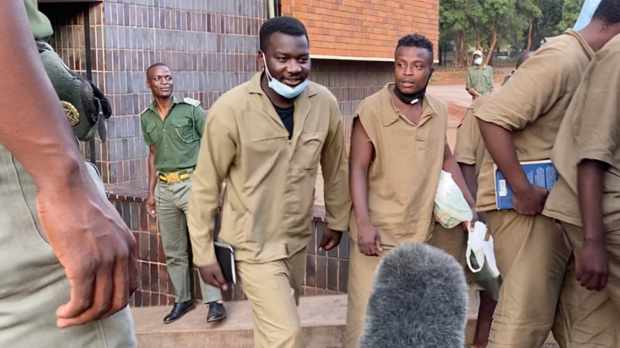 Makomborero Haruzivishe (with a book in hand) talking to reporters as he leaves Harare Magistrates Court on April 6, 2021 for Chikurubi Maximum Prison after being sentenced to 14 months in jail for inciting violence. (VOA/Columbus Mavhunga)