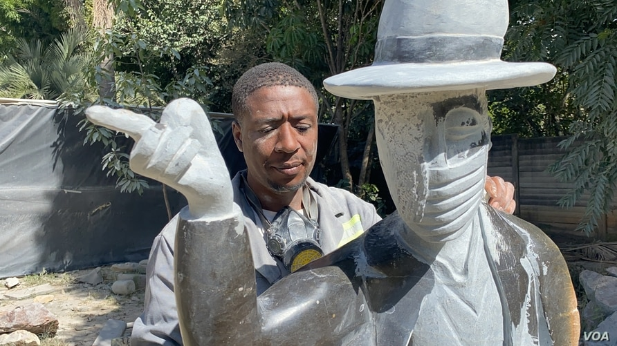 """David Ngwerume working on his most talkedabout piece, whichencourages people to mask up, in an exhibit called: """"MJ"""" namedafter the late U.S. pop icon""""MichaelJackson,"""" Harare, April 23, 2021. (ColumbusMavhunga/VOA)"""