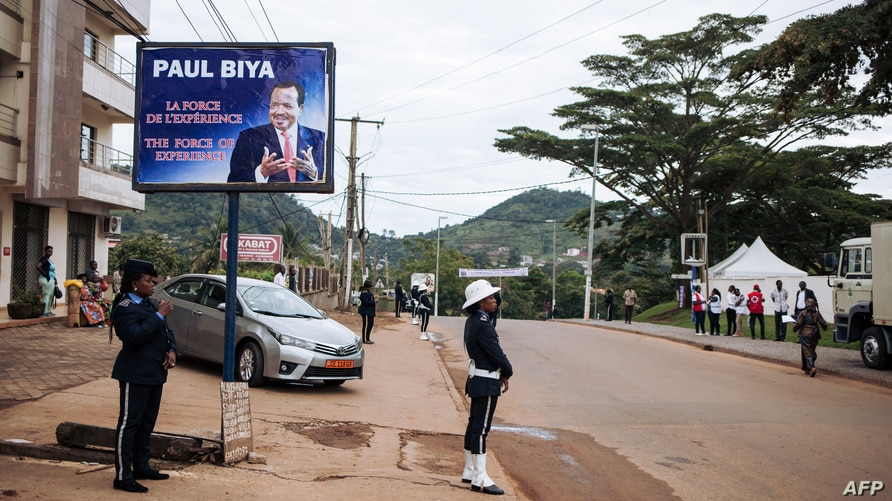 FILE - Police officers stand in front of the polling station where incumbent Cameroon President Paul Biya, is expected to vote, in Yaounde, Oct. 7, 2018. Biya's election win remain disputed by the opposition.