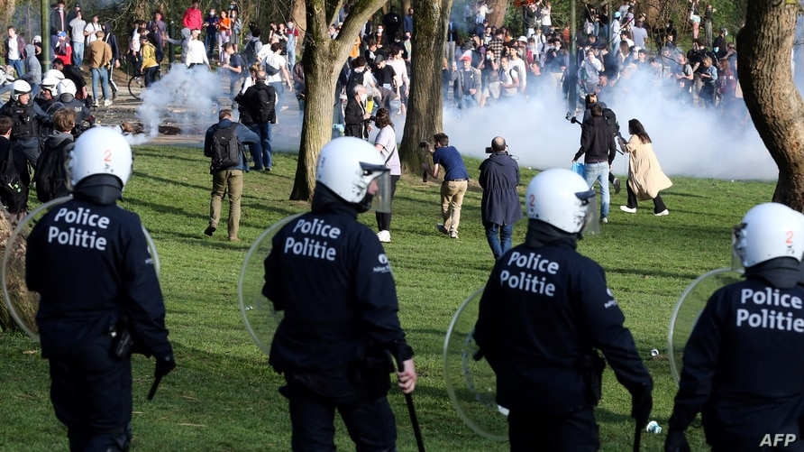 Belgian police officers surround people at the Bois de la Cambre park, in Brussels, on April 1, 2021, during an unauthorized rally for a fake concert announced on social media as an April Fool's Day prank.
