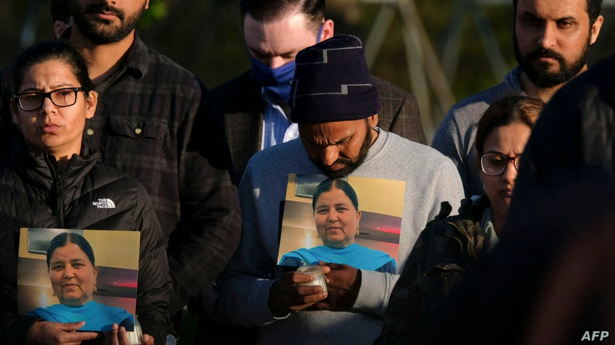 Family members hold a photo of their loved one during a candlelight vigil in Krannert Park in Indianapolis, Indiana, April 17, 2021, as they remember the victims of a mass shooting at a local FedEx facility.
