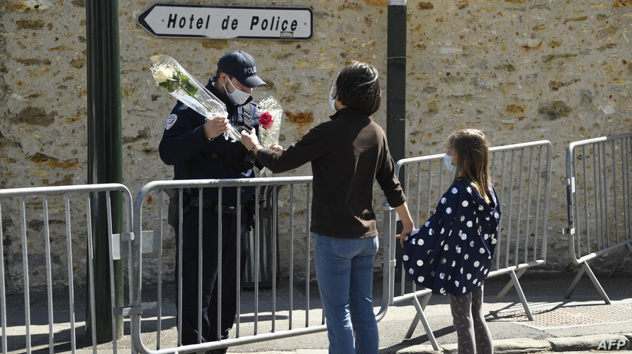 A woman hands flowers to an officer to be taken to the police station where a female police worker was stabbed to death two days earlier, in Rambouillet, southwest of Paris, France, April 25, 2021.