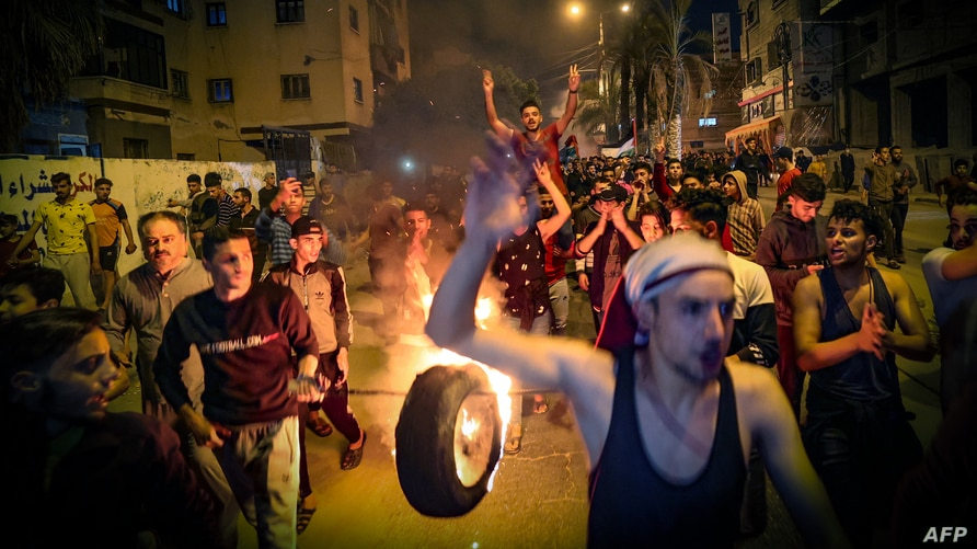 Palestinians parade a burning tire as they shout slogans during a rally in Gaza City, April 24, 2021.