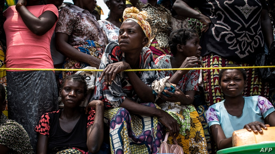 FILE - Women wait for their rations to be handed out at a food distribution site in Kasala, Kasai region, Democratic Republic of Congo, Oct. 25, 2017.