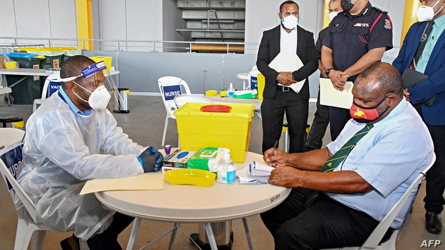 FILE - This photo taken March 30, 2021, shows Papua New Guinea's Prime Minister James Marape (R) preparing to receive a dose of the AstraZeneca COVID-19 vaccine, in Port Moresby, Papua New Guinea.