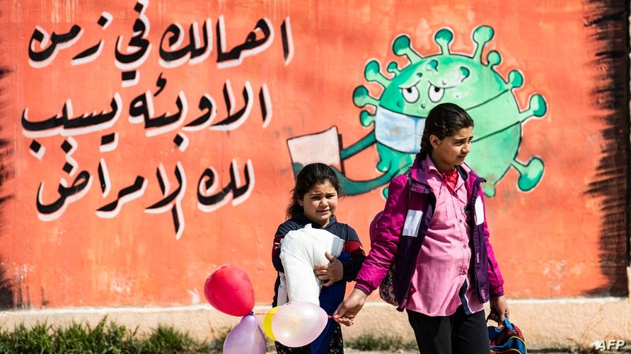 FILE - Children cross a street in front of a mural raising coronavirus awareness, in Syria's northeastern city of Qamishli, March 9, 2021.