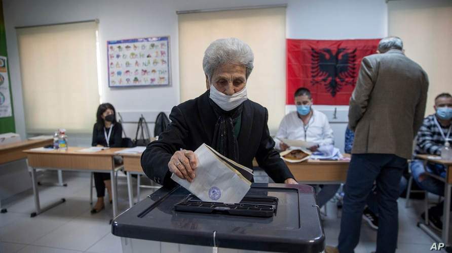 A woman casts her ballot during parliamentary elections in capital Tirana, Albania, April 25, 2021.