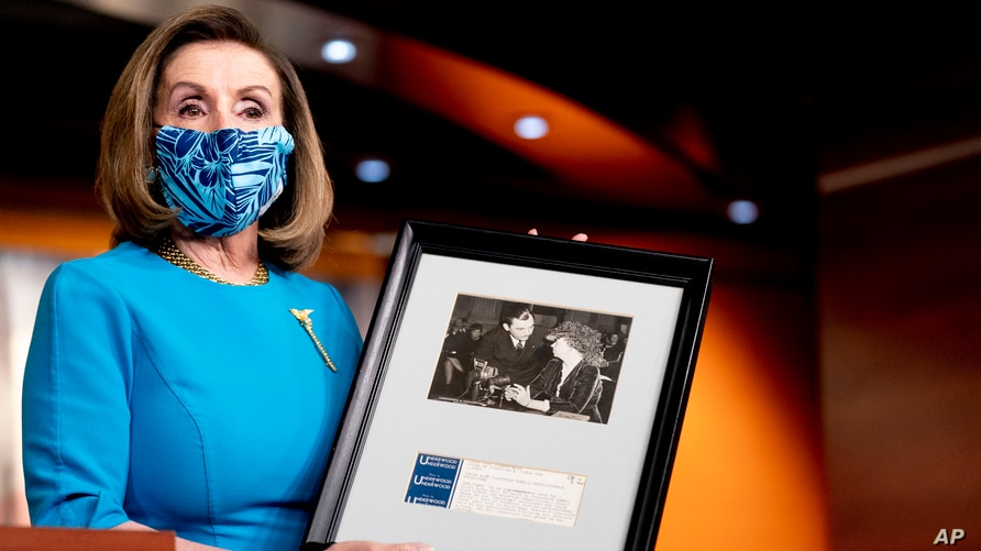 House Speaker Nancy Pelosi of Calif., holds up a photograph of her father, Thomas D'Alesandro Jr., with Eleanor Roosevelt, as she speaks about the long fight for DC statehood during her weekly press briefing on Capitol Hill, April 22, 2021, in Washington.