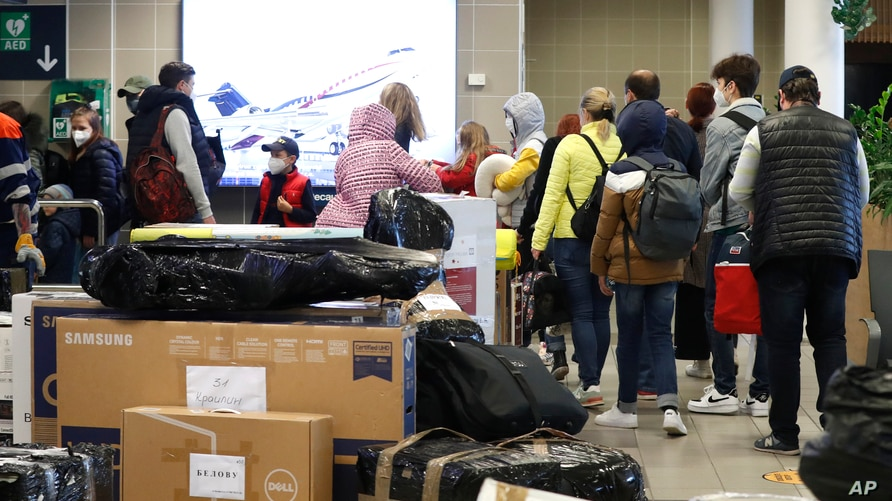 FILE - Russian diplomats with families wait in line to check in at the Vaclav Havel airport after a Russian special government plane landed in Prague, Czech Republic, April 19, 2021.