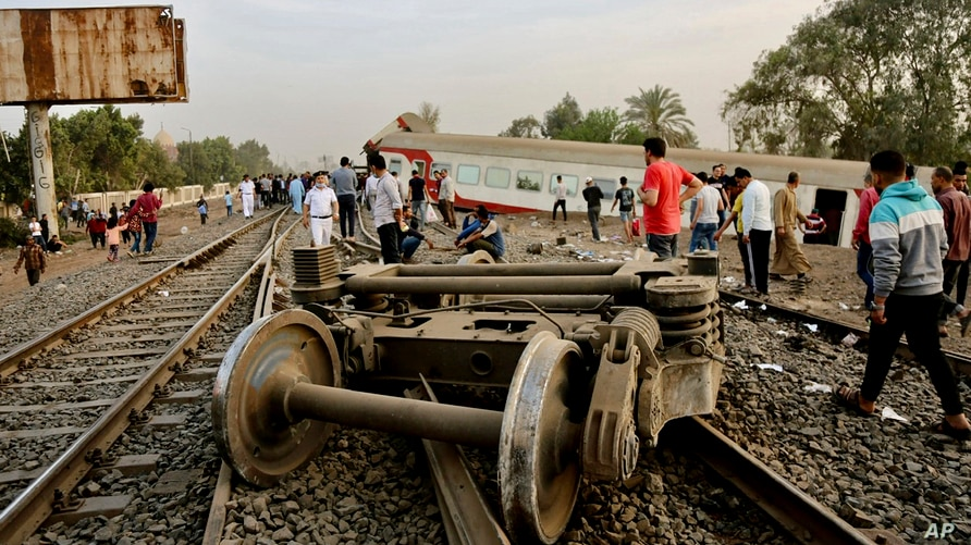 People gather at the site where a passenger train derailed injuring at least 100 people, near Banha, Qalyubia province, Egypt, April 18, 2021.