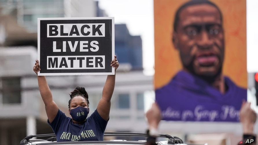 People hold up signs, including one with an image of George Floyd, outside the courthouse in Minneapolis, Minnesota, April 20, 2021, after former Minneapolis police officer Derek Chauvin was found guilty in the death of Floyd.