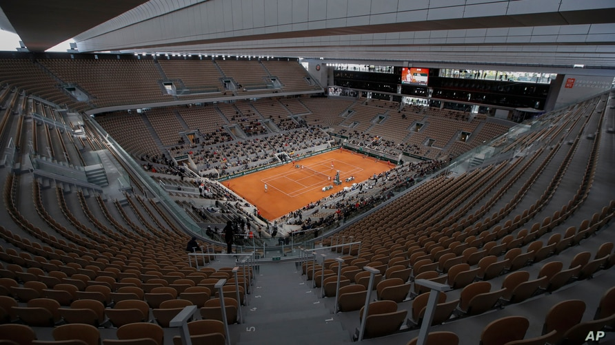 FILE - Rows of empty seats are seen at the Roland Garros stadium in Paris as Serbia's Novak Djokovic and Spain's Rafael Nadal warm up for the final match of the French Open tennis tournament, Oct. 11, 2020.