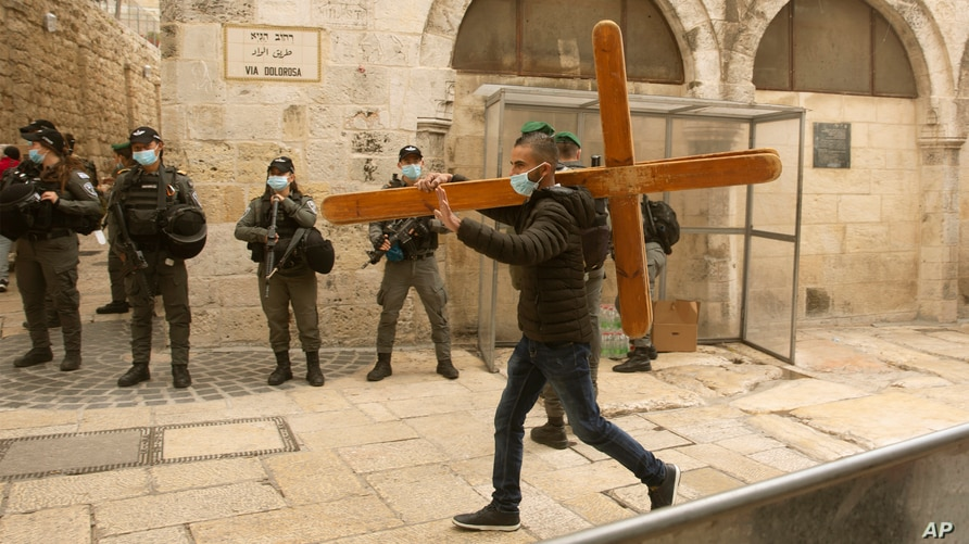 A man carries a cross along the Via Dolorosa ahead of the Good Friday procession towards the Church of the Holy Sepulchre, traditionally believed by many to be the site of the crucifixion of Jesus Christ, in Jerusalem's Old City, April 2, 2021.
